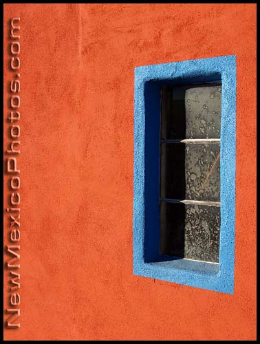 window with blue trim on an orange stucco wall