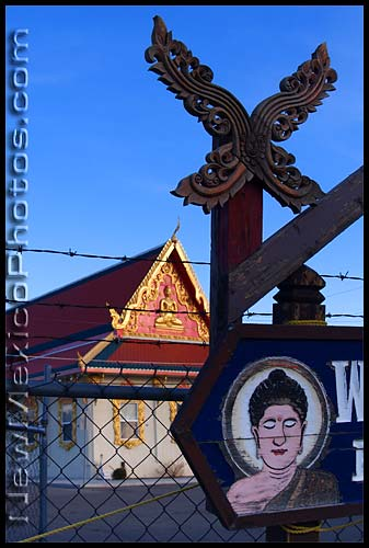 sign for the wat buddhamongkolnimit buddhist temple in Albuquerque, with the temple itself behind it