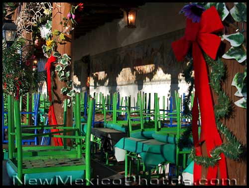 green chairs upside down on the tables of an Albuquerque Old Town restaurant's patio