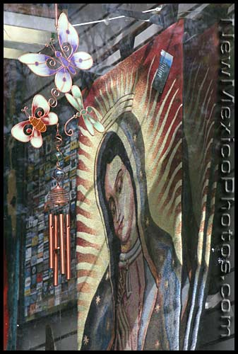 photo of a virgin of guadalupe tapestry seen through a store window