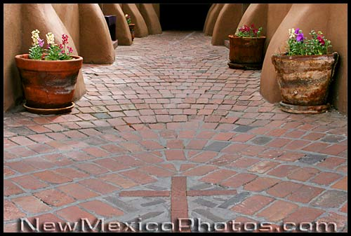 a walkway in Old Town Albuquerque incorporates bricks in the shape of a cross