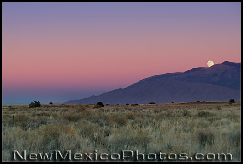 the full moon rises over the northern end of the Sandias