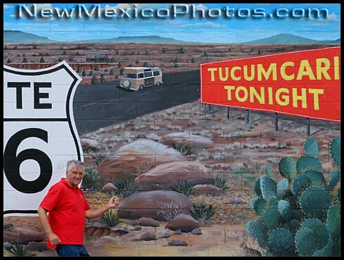 a traveler on old route 66 poses in front of a mural in tucumcari