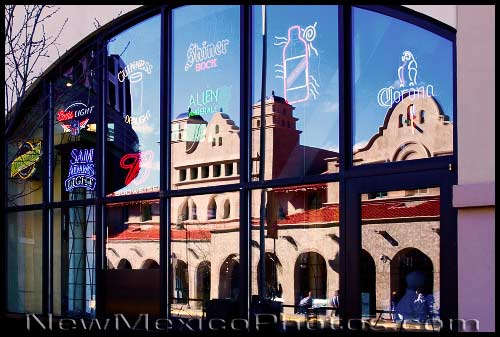 The Alvarado Transportation Center, in downtown Albuquerque, is reflected in the window of an eatery across the street