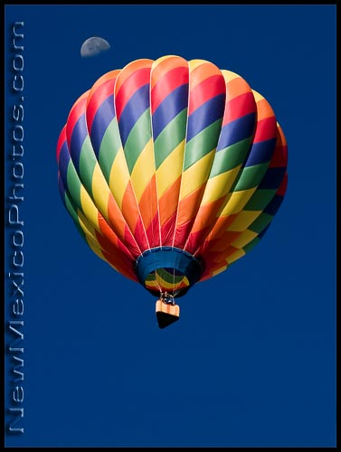 A colorful hot air balloon passes beneath a half moon