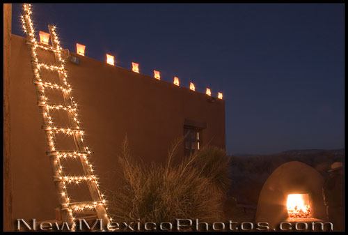 A ladder decorated with Christmas lights is accompanied by electric luminarias and a blazing fire in an horno at Coronado State Monument