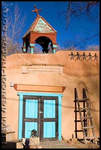 a building in Taos with a cross canted to one side