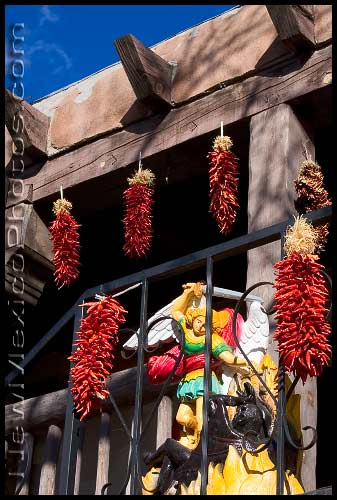 The balcony of a second-floor shop in Old Town Albuquerque is decorated with ristras and an avenging angel