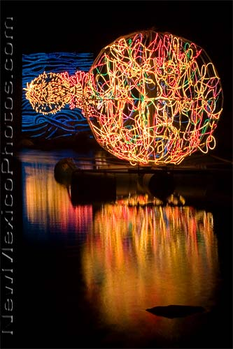 A large sphere -- lit with Christmas lights -- reflects in the pond at the Rio Grande Botanic Garden