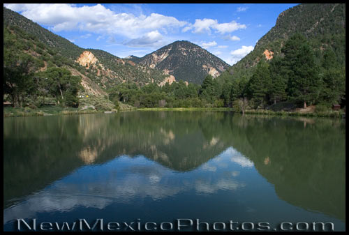 The mountains of northern New Mexico are reflected in a pond near Questa
