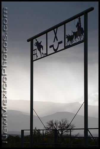 ranch gate silhouetted by a distant rainstorm in the Sandia Mountains