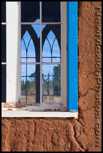 Looking through an old window pane to another window on the other side of San Rafael Mission Church in La Cueva