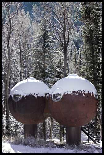 A pair of spherical structures nestle together amidst snowy trees in the mountains outside of Questa