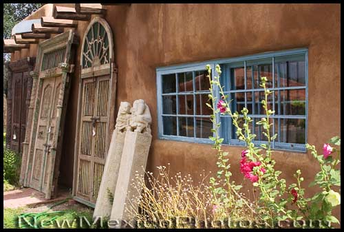 Pairs of doors lined up against a stucco building in Taos are framed by hollyhocks