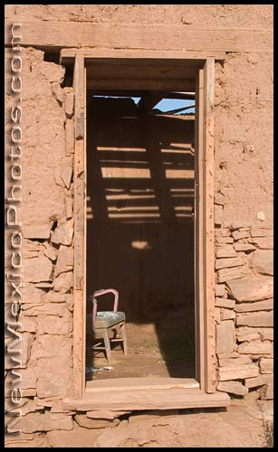 An abandoned chair within the ruins of an adobe building, as seen through a window
