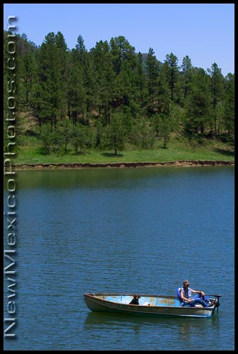 A man and his dog in their boat, drifting in Lake Maloya at Sugarite Canyon State Park