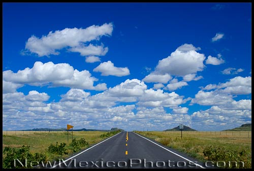 A seemingly endless road meets the horizon and a classic New Mexican sky