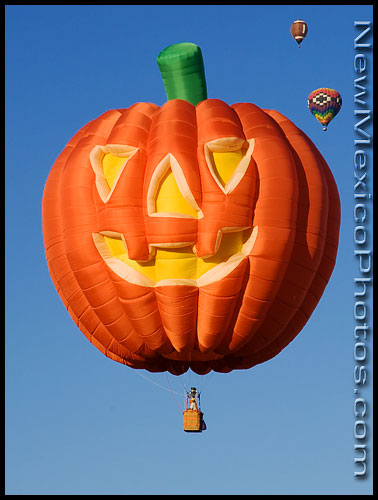 A Jack-O-Lantern special shapes hot air balloon floats in the sky, shortly before Halloween