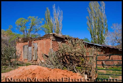 A small adobe building made out of the red clay of the Jemez