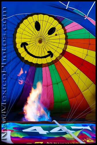 A hot air balloon, with a smiley face at the top, inflates at the Albuquerque International Balloon Fiesta