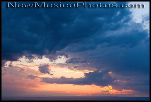 Glowering clouds frame a summer sunset seen from the Sandia foothills