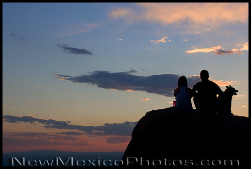 A couple and their dog savor a mid-summer New Mexican sunset