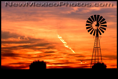 A windmill silhouetted by a classic New Mexican sunset
