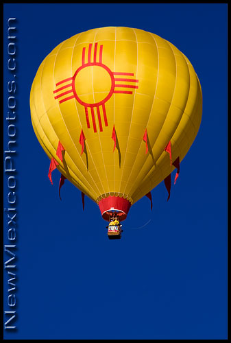 A hot air balloon with a zia, the state symbol, rises into the sky on the first morning of the Balloon Fiesta