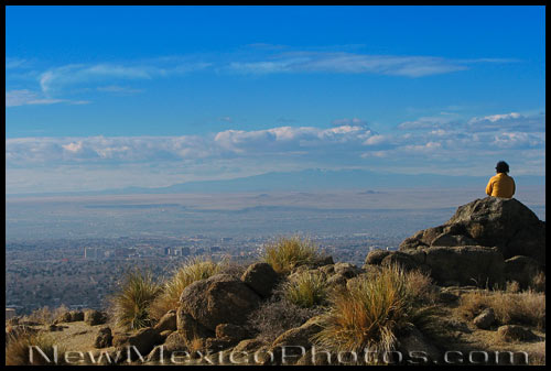 A hiker in the Sandias contemplates all of Albuquerque's wide and impressive skyline, including Mt Taylor and the volcanoes