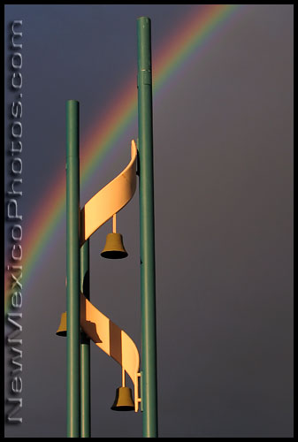 The bell tower of an Albuquerque church is framed by a late afternoon rainbow