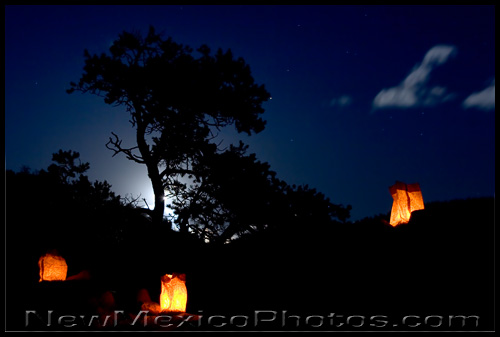 three luminarias, aka farolitos, and a silvery winter moonrise