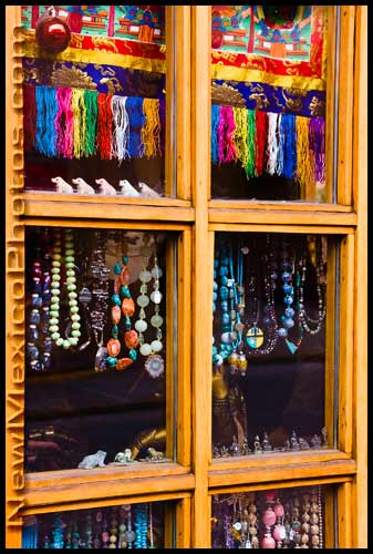 a shop window in Santa Fe is adorned with beads and a single Christmas ornament