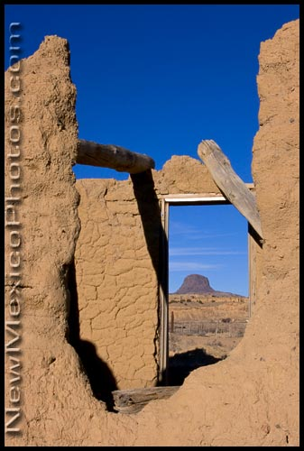 Cabezon, a volcanic plug in northwestern New Mexico, is seen through the ruins of a house in Guadalupe