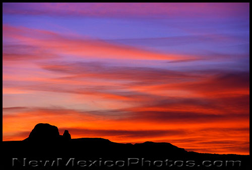 a butte in the rio puerco valley is silhouetted by the setting sun