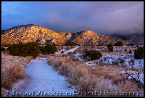 light breaks through the clouds at the end of a snowy day in the Sandia foothills