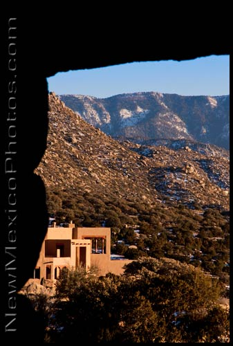 looking through the window of a CCC stone cabin at a residential area nestled in the foothills of the Sandias